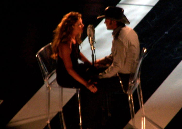 Faith Hill and Tim McGraw singing a song on stage during the taping for a 2-hour TV special