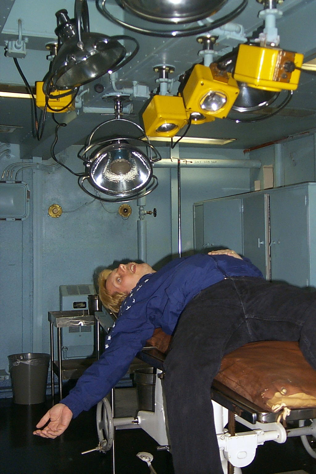 Dennis is passed out on the operating table in Sick Bay from running up and down the ladders aboard the ship.